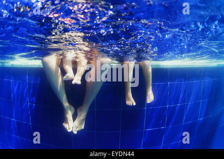 Underwater photo of young family, mother with children - a baby boy and a little girl sitting on the blue swimming - Stock Photo