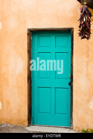 Old Pueblo Spanish style building with adobe walls enhanced by blue door with hanging red peppers. - Stock Photo