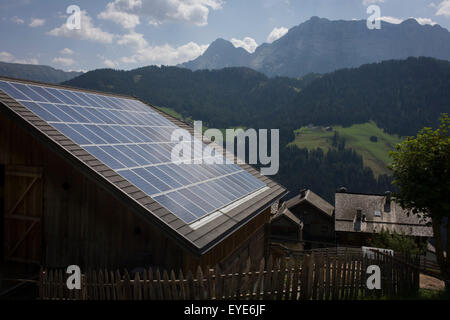 Solar panels on the roof of a Dolomites farm's barn roof in the old rural hamlet of Aireië, near Wengen-La Val, - Stock Photo