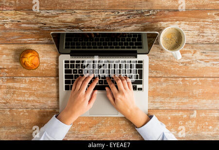 close up of female hands with laptop and coffee - Stock Photo
