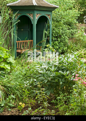 Ornate arched, wooden, garden gazebo arbor amongst overgrown, green foliage, Barnsdale Gardens, Rutland, England, - Stock Photo