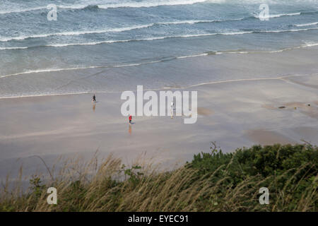 Looking down on people walking on the beach as the tide goes out - Stock Photo