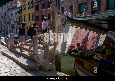 Pedestrians and tourists walk over a canal bridge with shadows on an afternoon sun screen in Dorsoduro - Stock Photo