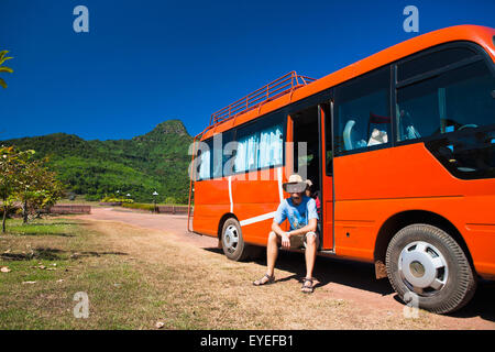 A man sits and waits in a tour bus after a temple tour; Wat Phu, Loas - Stock Photo