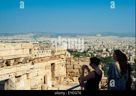 Tourists take pictures of ruins, view from the Acropolis; Athens, Greece - Stock Photo