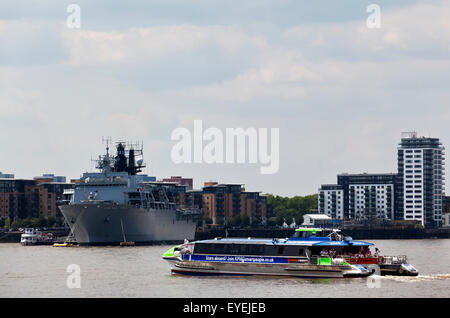 View of the River Thames, a transport for London commuter boat, and the HMS Ocean docked at Greenwich; London, England - Stock Photo