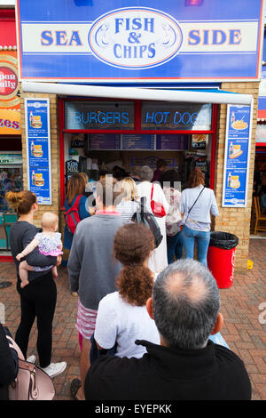 People queue for fish and chips at the seaside - Stock Photo