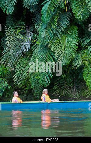 Tourists river boating at Ulu Temburong National Park; Brunei - Stock Photo