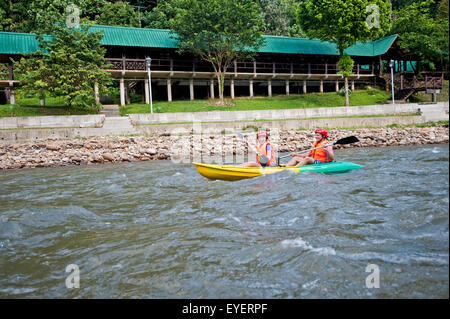 Tourists paddling in a canoe in Ulu Temburong National Park; Brunei - Stock Photo