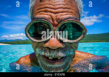 Portrait of local fisherman in the water wearing goggles; Jaco Island, Timor-Leste - Stock Photo