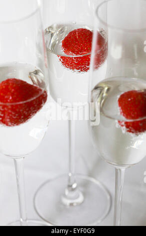 Three glasses of champagne cocktails against a white backdrop