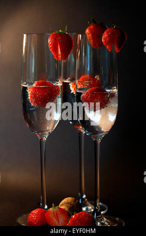 Three glasses of champagne cocktails against a dark backdrop