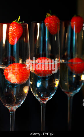 Three glasses of champagne cocktails against a black backdrop