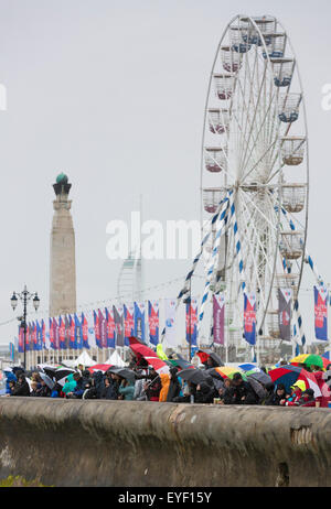 Rain soaked fans watch the six competing AC45 foiling catamarans during practice racing at the America's Cup World - Stock Photo