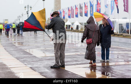 Rain soaked fans battle the elements as they watch the six competing AC45 foiling catamarans during practice racing - Stock Photo