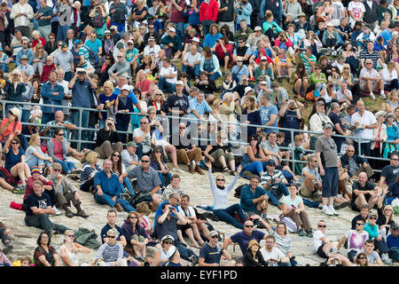 Fans cheer on Sir Ben Ainslie's AC45 catamaran from their shoreline vantage points during the first day's competition - Stock Photo