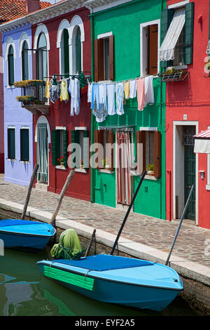 Blue boats sit in front of a row of colourful houses; Burano, Venice, Italy - Stock Photo