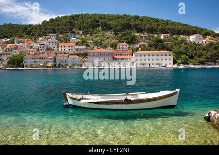 A small boat rests in the tranquil clear water; Pucisca, Island of Brac, Croatia - Stock Photo