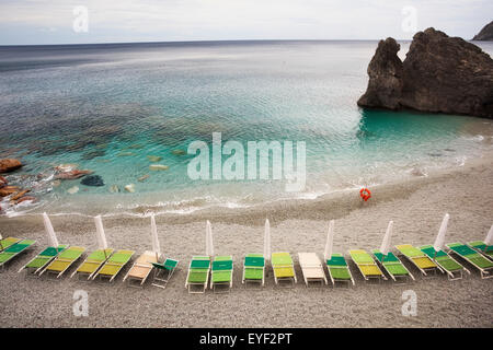 Beach chairs along the water's edge and a view of the horizon; Monterosso Al Mare, Liguria, Italy - Stock Photo