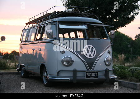 A TWO-TONE GREY RETRO MODIFIED 1962 VOLKSWAGEN VW CAMPER BUS TAKEN AT DUSK WITH THE SUNSET BEHIND THE VEHICLE - Stock Photo