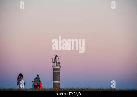 A family walks at sunset with a view of the top of the lighthouse; Cabo Polonio, Uruguay - Stock Photo