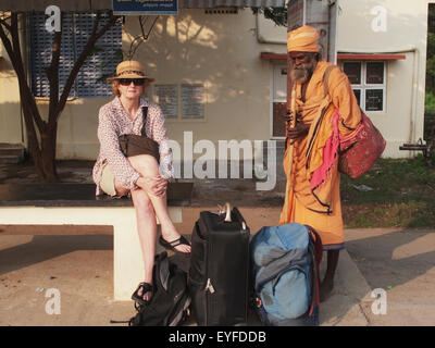 Female tourist waiting at train station and being watched by a sadhu at kanchipuram station; kanchipuram tamil nadu - Stock Photo