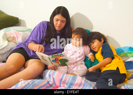 An Asian American teen baby sitter reads to her infant sister and younger brother in bed at home in Laguna Beach, - Stock Photo