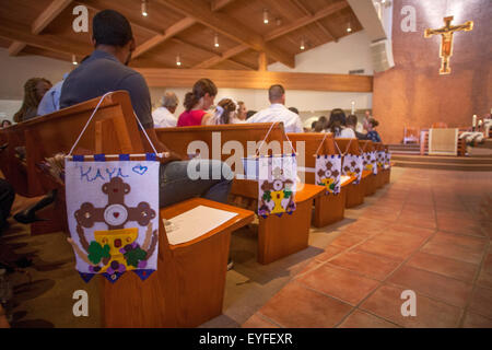 First Holy Eucharist banners are pew markers at a Laguna Niguel, CA, Catholic church mass for First Communion ceremonies. - Stock Photo