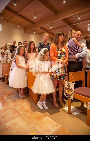 Wearing formal First Communion outfits, multiracial children and their parents attend mass at a Laguna Niguel, CA, - Stock Photo