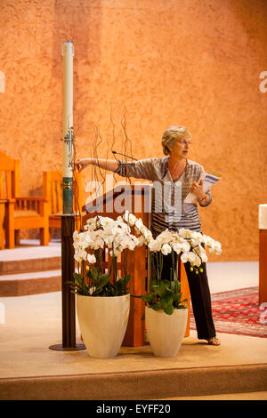 At a Laguna Niguel, CA, Catholic church, a volunteer teacher explains the significance of a ceremonial candle to - Stock Photo