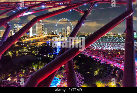Singapore skyline including Singapore Flyer Ferris wheel, seen through support beams from observation deck on SuperTree - Stock Photo