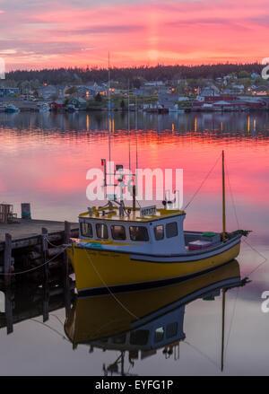 Red sky over Louisbourg harbor at sunset, Louisbourg, Nova Scotia, Canada - Stock Photo