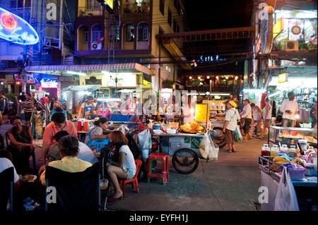 Street traders, locals and tourists mingle along the Khao San Road at night; Bangkok, Thailand - Stock Photo
