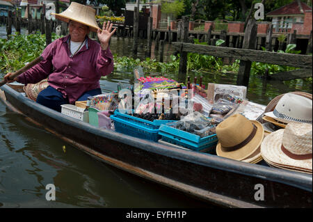 Thai woman in small river boat selling goods; Bangkok, Thailand - Stock Photo