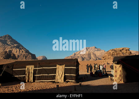 Tourists waiting to be picked up after spending the night in a Bedouin camp in the middle of the Wadi Rum desert; - Stock Photo