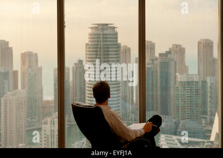 Man in office looking out from large windows to office and residential tower blocks in Dubai Marina; Dubai, United - Stock Photo