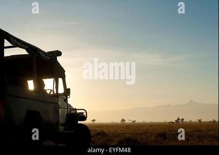 Silhouette of driver in 4x4 in front of Mt Kenya at dawn, Ol Pejeta Conservancy; Kenya - Stock Photo