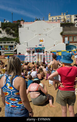 Children and parents watching a Punch and Judy puppet show at Viking Bay; Broadstairs, Kent, England - Stock Photo