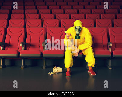 the man in a protective coverall  sitting in an empty theater - Stock Photo