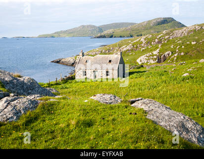 Deserted derelict croft cottage in coastal location on Vatersay Island, Barra, Outer Hebrides, Scotland, UK - Stock Photo
