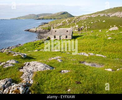 Deserted derelict croft cottage in coastal location on Vatersay Island, Barra, Outer Hebrides, Scotland, UK - Stock Photo