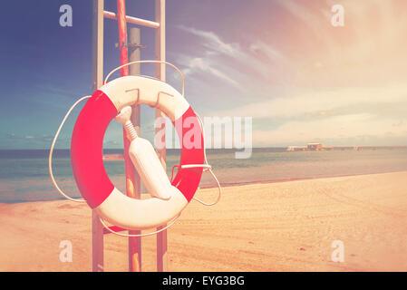 Lifebuoy, Red and White Life Preserver on Sandy Beach of Coastal Summer Vacation Resort, Vintage Retro Toned Image - Stock Photo