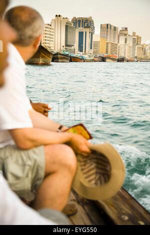 UAE, Tourists riding small ferry on Dubai Creek; Dubai - Stock Photo