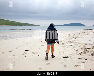Woman walking overcast sky sandy beach Eoligarry, Barra, Outer Hebrides, Scotland, UK - Stock Photo