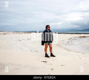 Woman standiing overcast sky sandy beach Eoligarry, Barra, Outer Hebrides, Scotland, UK - Stock Photo