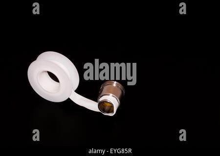 Teflon tape or plumber tape applied on a thread black background - Stock Photo