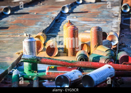 Used graffiti spray cans laying around - Stock Photo