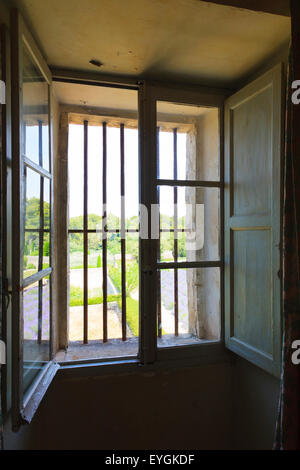 Old inward opening window with bars looking out onto garden - Stock Photo