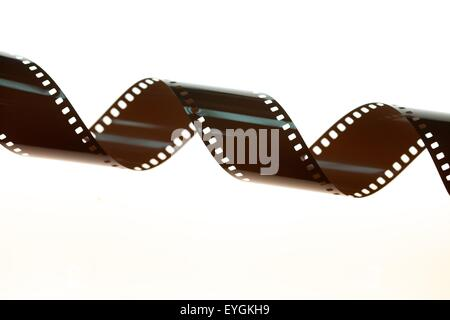 A twirled 35mm negative film strip on a light box in processing lab - Stock Photo