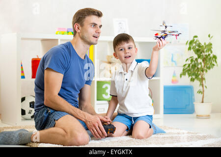 Father and his son play with RC helicopter toy - Stock Photo